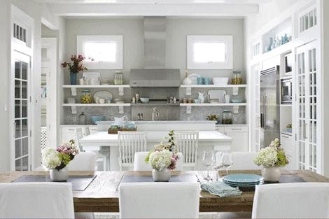 An open kitchen dining room space with white kitchen cabinets, gray